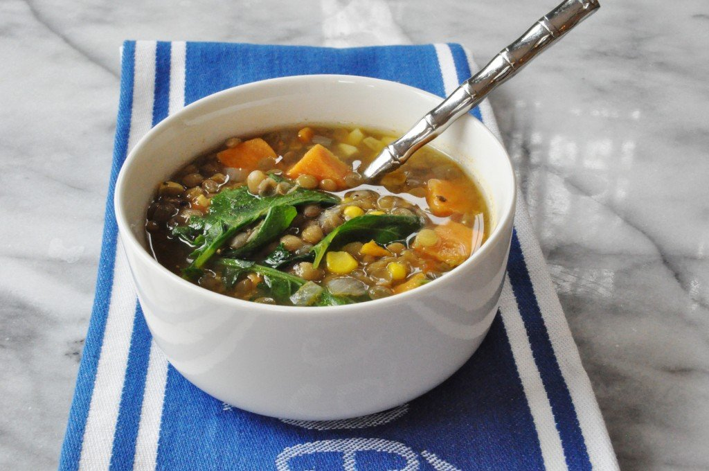 A white bowl filled with vegetable soup with a silver spoon in it on a blue and white towel on a marble bo
