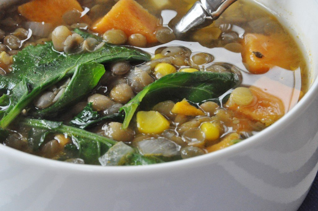 A close up of vegetable soup in a white bowl with a silver spoon in the bowl