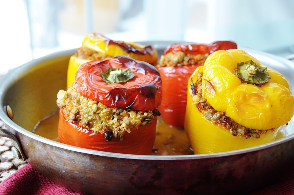 Vegan Lentil Quinoa and Vegetable Stuffed Peppers in a roasting pan with the lids of the peppers on top