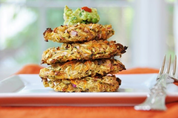 A stack of four Vegan Oil-Free Zucchini & Carrot Fritters with a dollop of guacamole on top on a square whit plate with a silver fork on an orange napkin