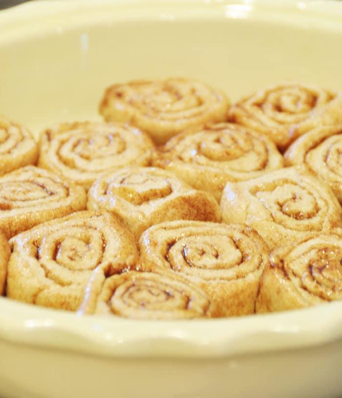 Raw Homemade Vegan Cinnamon Rolls ready to bake in a yellow pan
