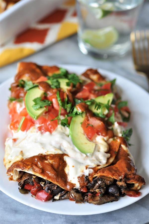 Two black bean and mushroom enchiladas on a white plate, garnished with chopped cilantro, tomato, and sliced avocado.