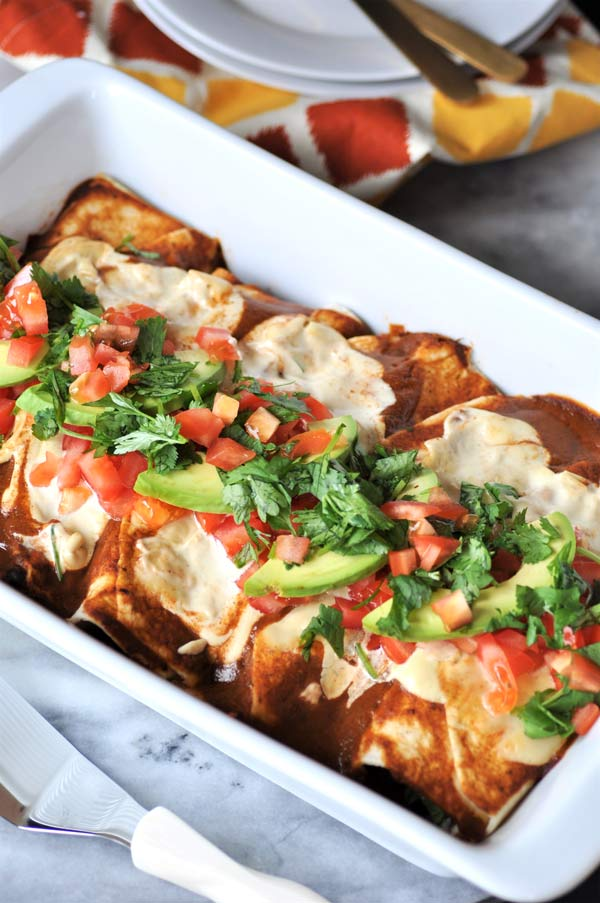 A white pan full of vegan black bean & mushroom enchiladas with sliced avocado, cilantro, and chopped tomato on top.