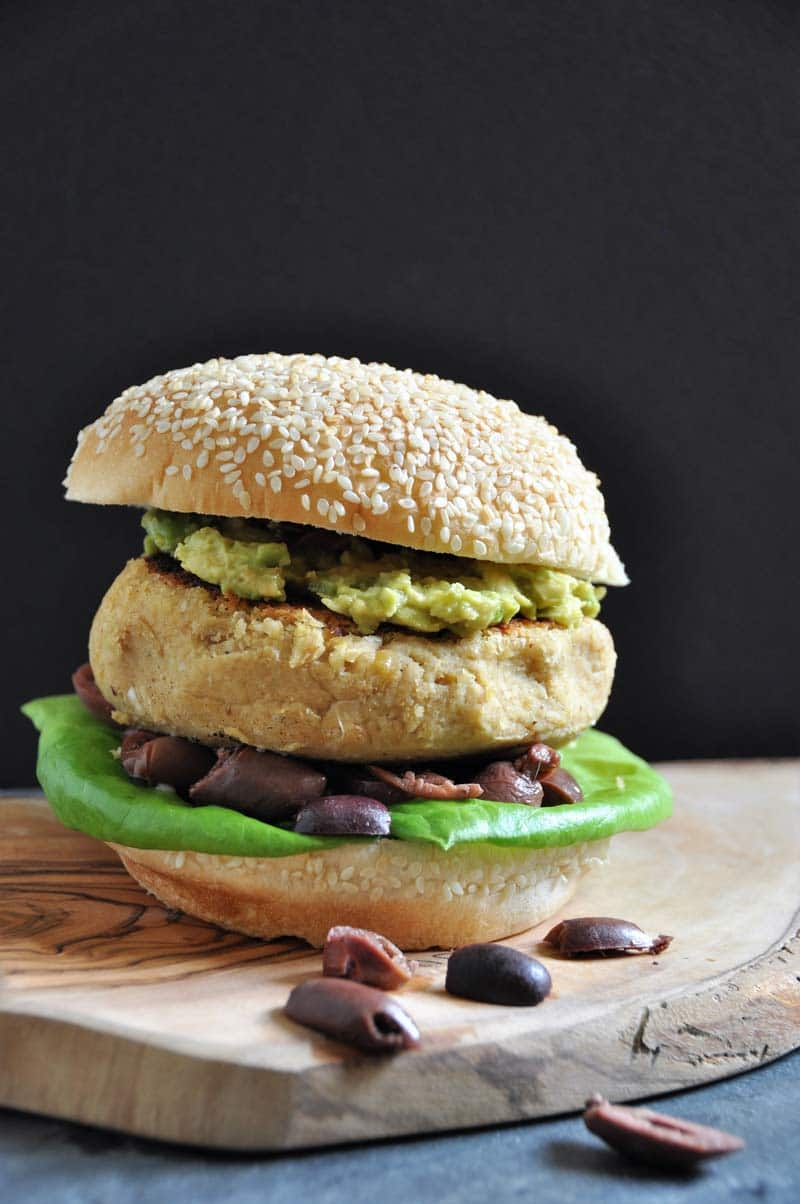A Hummus Burger on a wood board with olives falling out of it.
