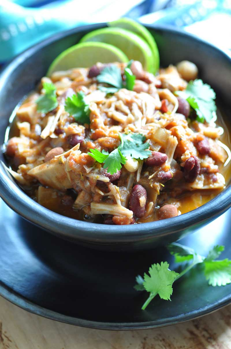 Jamaican Jerk Chik'n Chili in a black bowl on a balck plate with three lime wedges and sprigs of cilantro