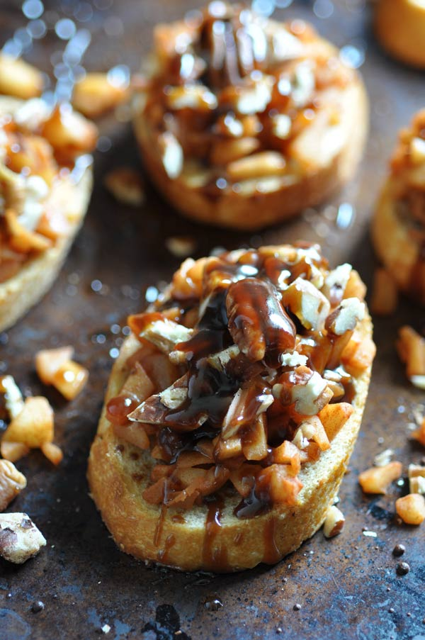 Apple Cinnamon Bruschetta on a baking sheet with chopped pecans scattered around the pan