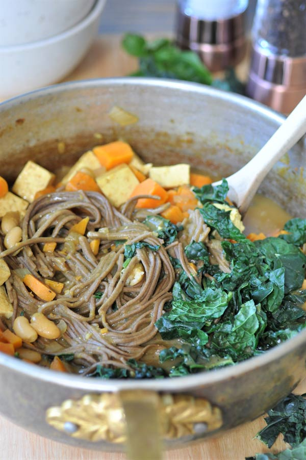 A copper pot of soba noodle soup with kale, sweet potato, tofu, and white beans being stirred with a wooden spoon.