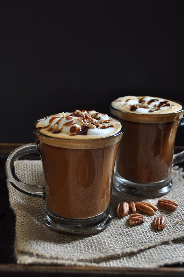 2 clear glass mugs of Maple Pecan Lattes on burlap with pecans scattered and a black background