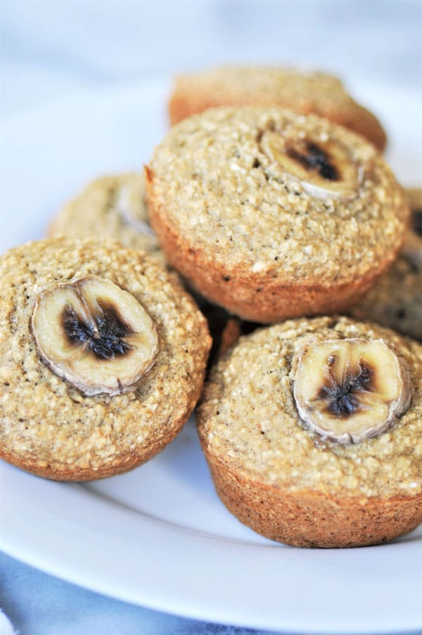 A close up shot of a pile of vegan and gluten-free banana muffins on a white plate