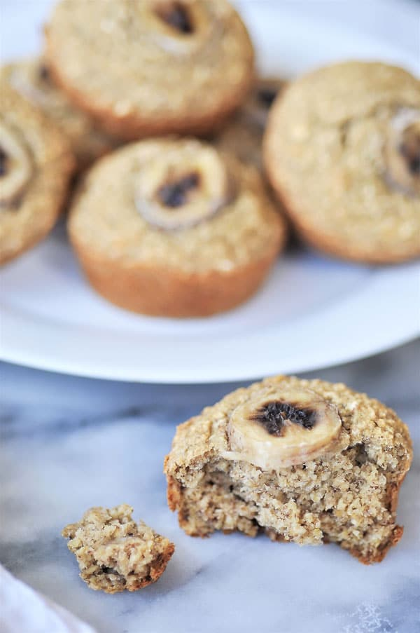 Healthy banana muffins piled on a white plate with one half eaten muffin on the marble surface
