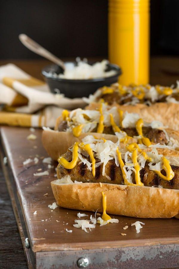 3 vegan grilled bratwurst with sauerkraut and yellow mustard on a wood board.