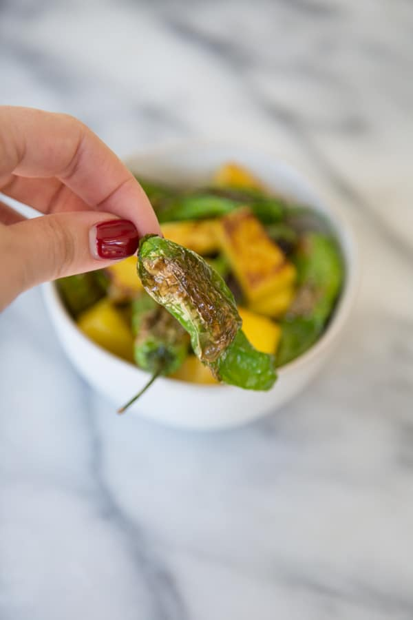Shishito peppers being held in front of a white bowl filled with peppers and pineapple on a marble board