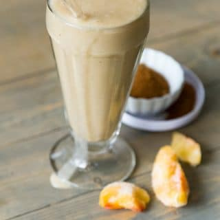 Peach Cobbler Smoothie with peaches and spices in the background on a wood cutting board.
