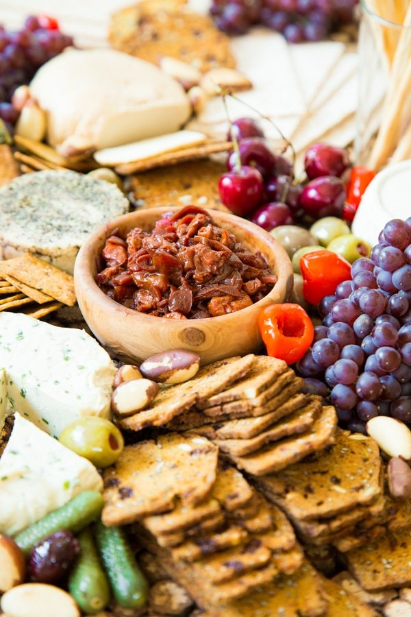 Cherry Confit on a cheese platter with vegan nut cheeses, grapes, peppers, olives, and a variety of crackers