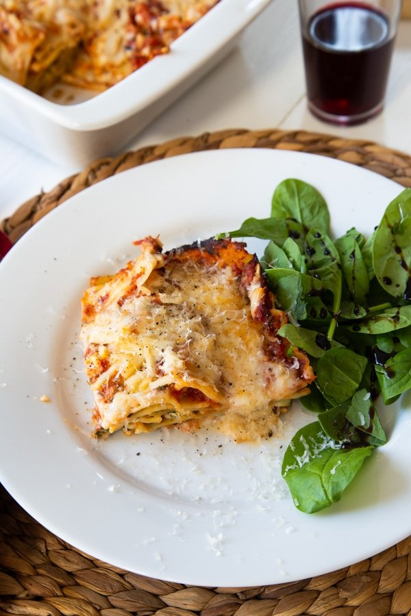 Vegan spinach lasagna and a side salad on a white plate on a braided wicker placemat, and a white ceramic pan of lasagna and a glass of red wine in the background