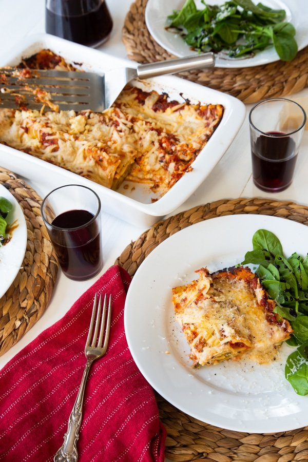 A slice of vegan spinach lasagna on a white plate with a side salad, and another plate of food on a wicker place mat and a white ceramic pan of lasagna in the background
