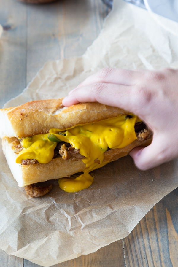 Philly Cheesesteak being held on a piece of unbleached parchment paper with cheese sauce running off the side