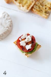 caprese sandwich with avocado pesto, grilled tomato, basil, and vegan mozzarella on a white board with a wheel of mozzarella