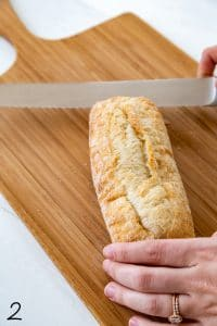 baguette being cut in half with serrated knife on a wood cutting board on top of white wood