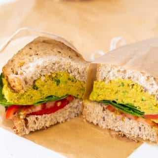 A smashed chicikpea salad sandwich cut in half and wrapped in parchment paper