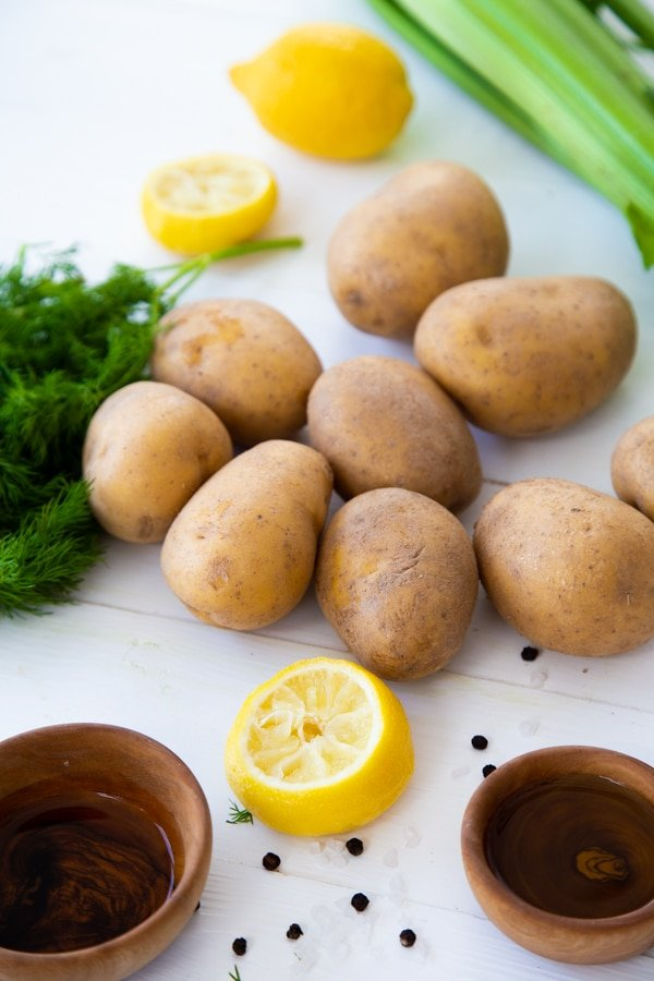 Several whole potatoes, lemon halves, celery, fresh dill and wood bowls with vinegar on a white table.