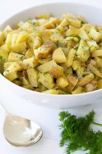 Potato salad in a white bowl with a bunch of dill and a spoon on the side of the bowl.