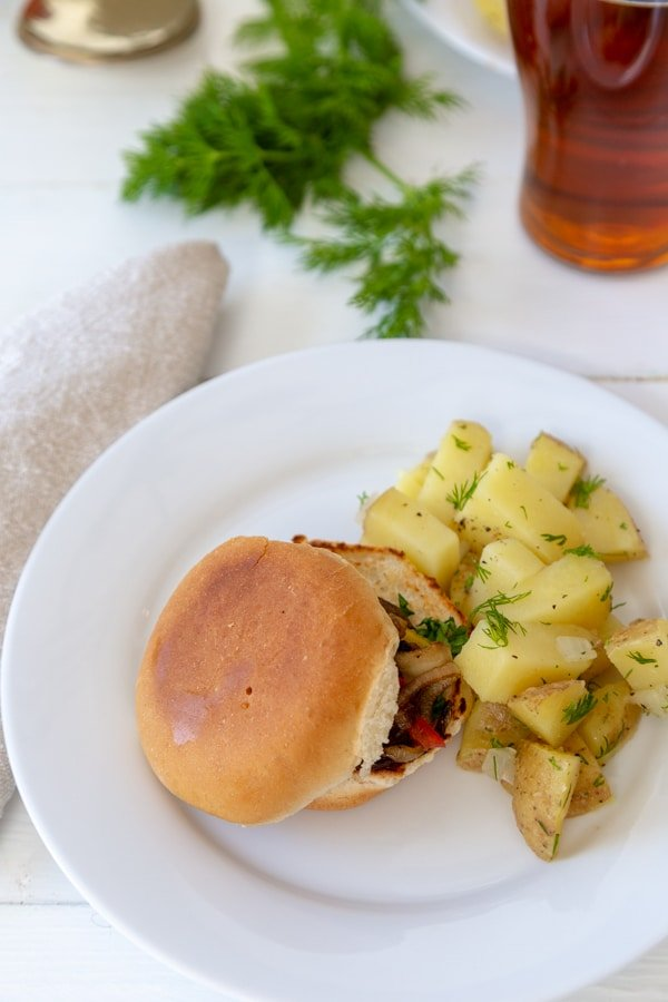 A white plate with a mushroom slider and potato salad, and a glass of beer and fresh dill in the background.