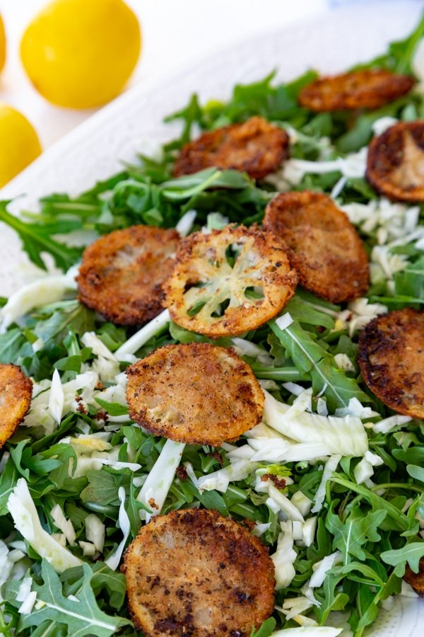 An arugula and fennel salad with fried lemons and a creamy dressing with lemons in the background
