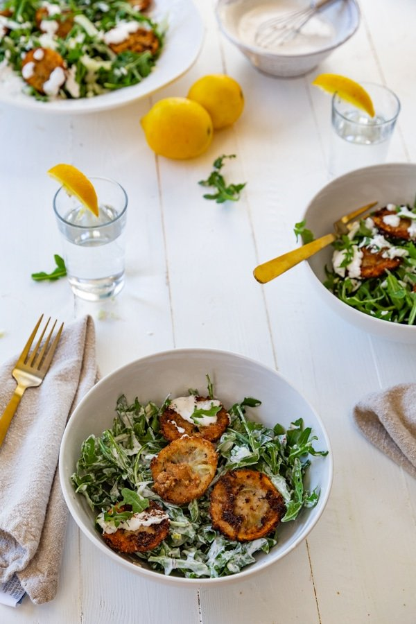 Arugula and fennel salad with fried lemons in three white bowls with salads and lemons on the table and gold utensils.