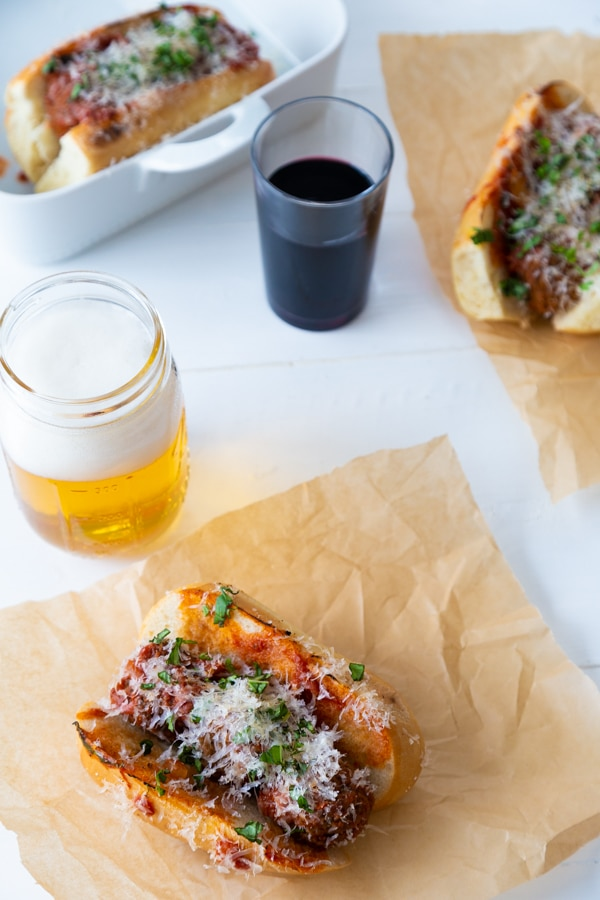 3 of our vegan meatball sub on parchment paper with a beer and a glass of wine next to them.