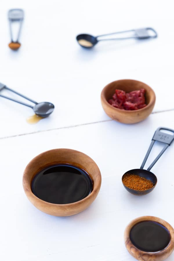 Wooden bowls and black measuring spoons with spices and liquids