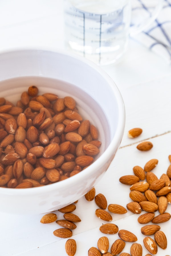 Process shot of a white bowl with almonds soaking in water and almonds scattered on a white table.