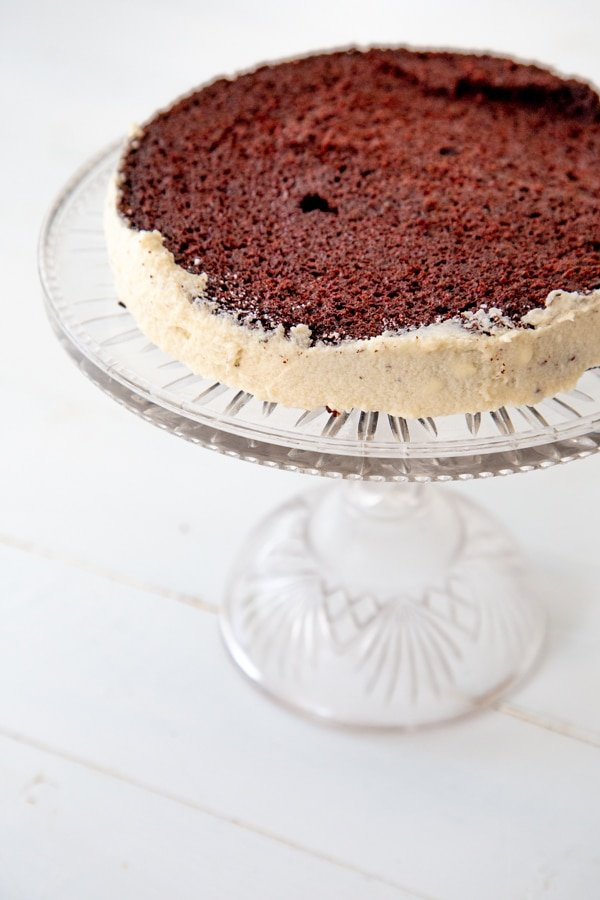 The bottom half of a chocolate cake on a glass cake stand with white frosting on the sides.