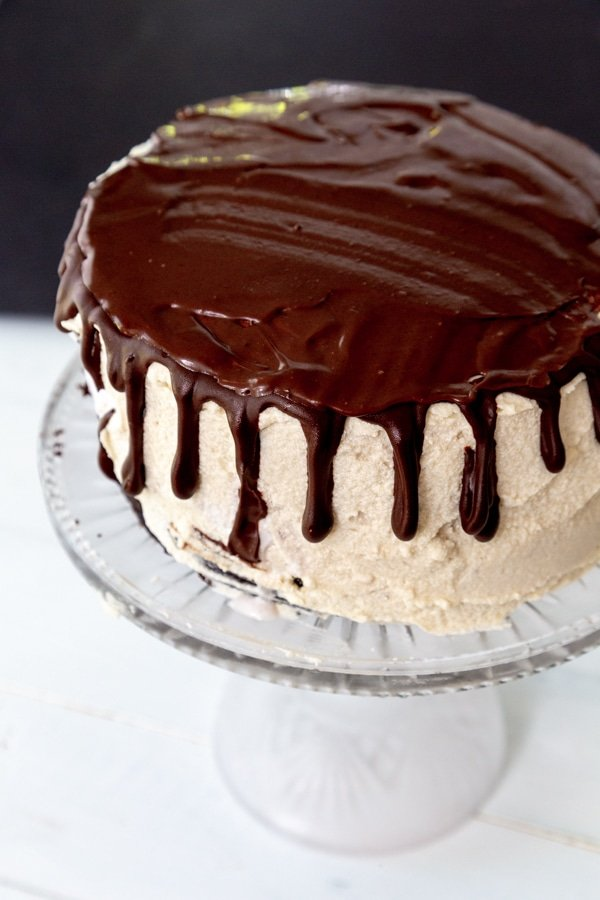 A cake with vanilla frosting and chocolate ganache dripping down the sides and on the top of the cake.