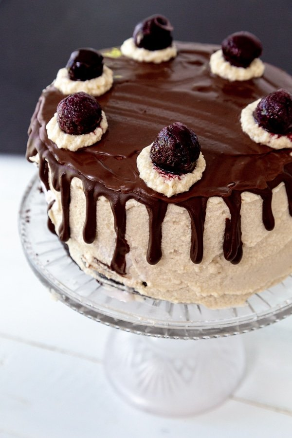 A cake with vanilla frosting and chocolate ganache on top and dripping down the sides with dollops of frosting and cherries on top of the dollops.
