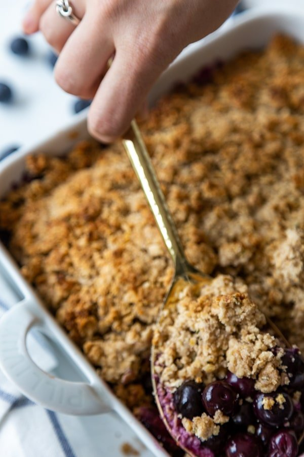 A hand holding a spoon, scooping out a serving of blueberry crumble from a pan.