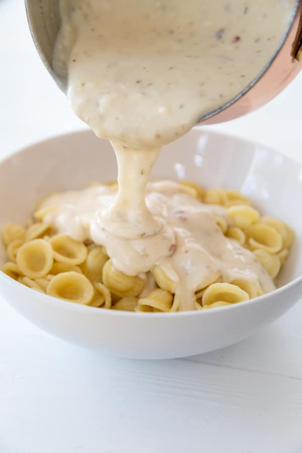 Pasta in a white bowl with a pan of cream sauce being poured on top of it.