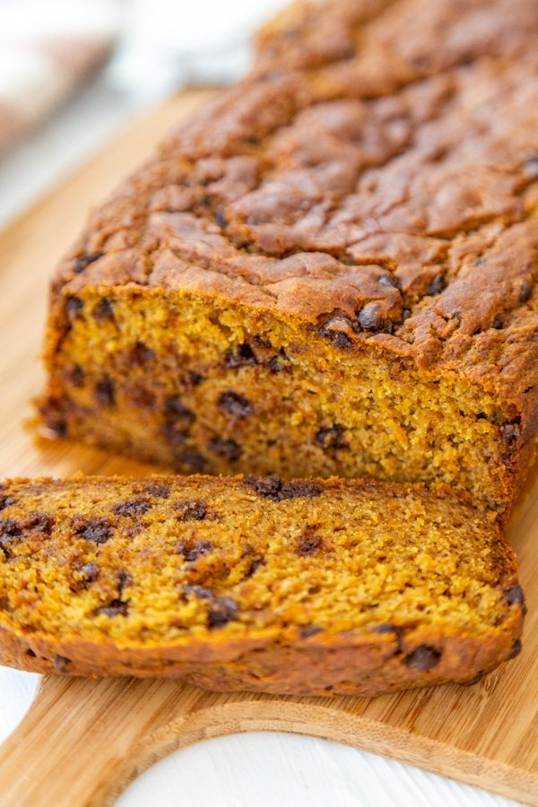 A loaf of pumpkin bread with chocolate chips and a slice off of the end on a wood board.