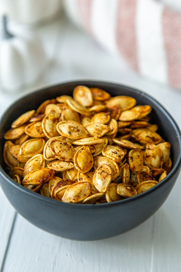 A black bowl with spicy roasted pumpkin seeds.