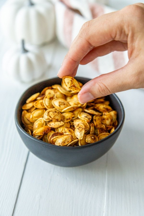 A hand picking up roasted pumpkin seeds from a black bowl.