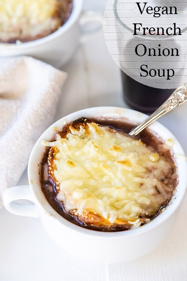 Vegan french onion soup with stretchy vegan cheese, baguette, and a red wine onion broth in a white soup bowl served with a glass of red wine