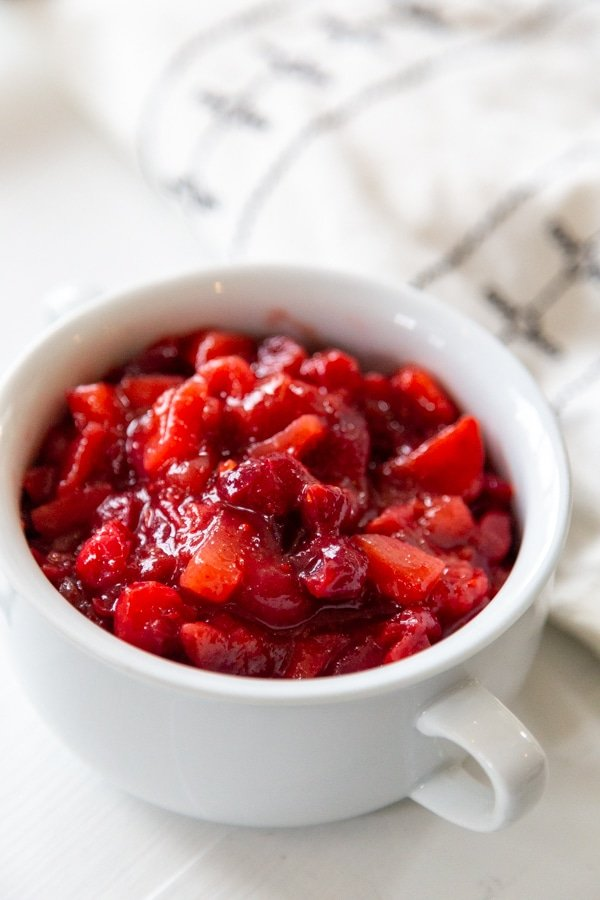 A white bowl with cranberry apple sauce next to a black and white napkin.