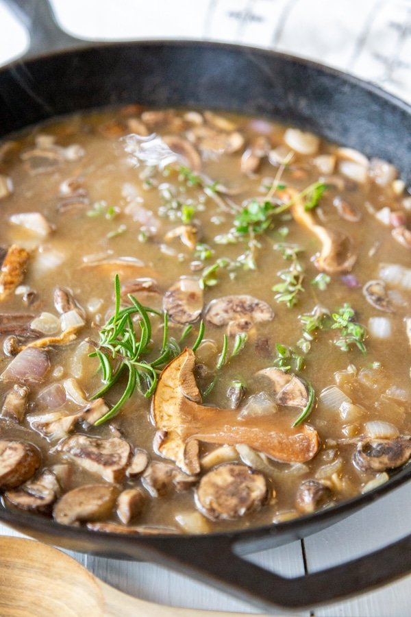 An iron skillet with mushrooms and gravy.