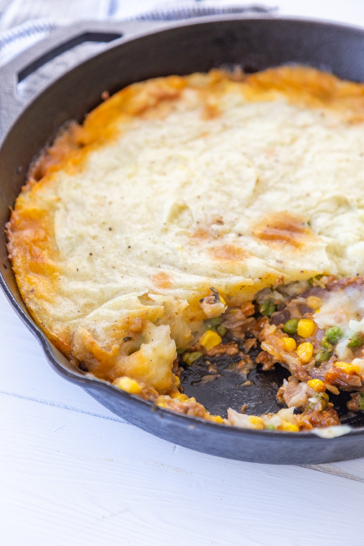 An iron skillet with a sheperd's pie and a portion removed from the pan.