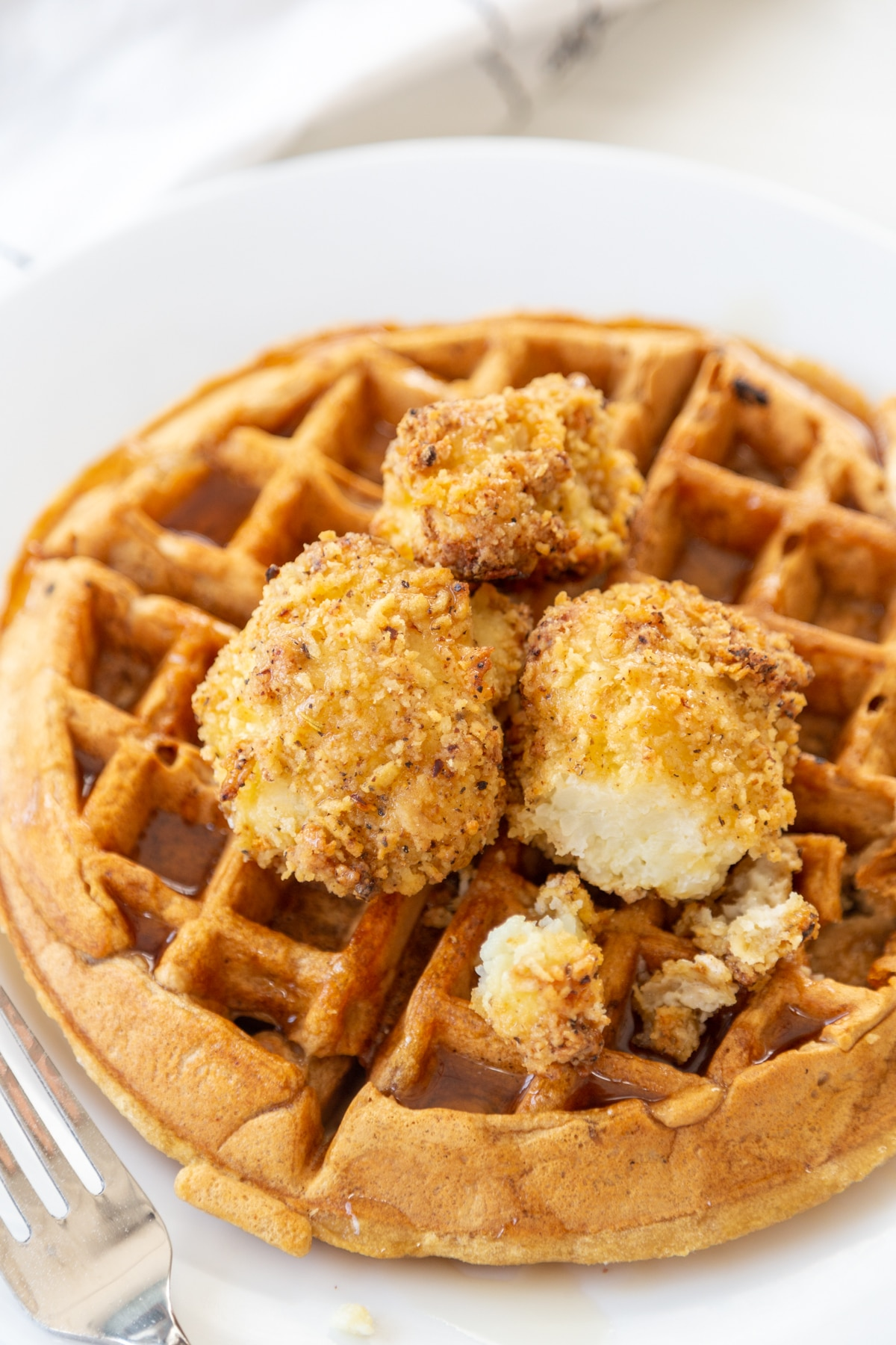 A Belgian waffle on a white plate with crispy cauliflower and maple syrup on top. A silver fork is next to the plate.